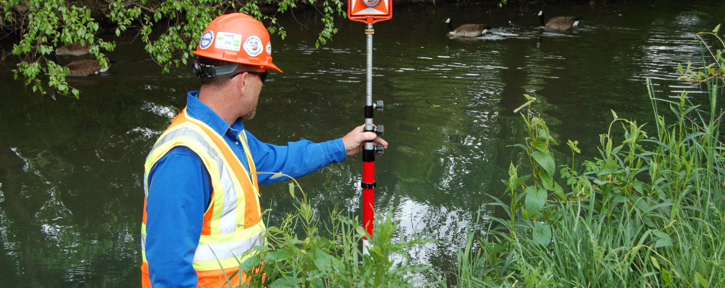 A scientist measures water depth in a stream and wetland environment.