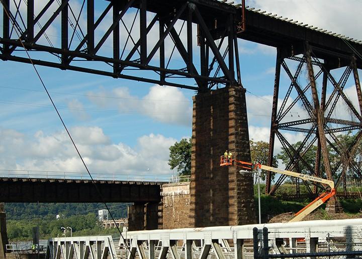 Bridge inspectors on a lift at a train trestle bridge